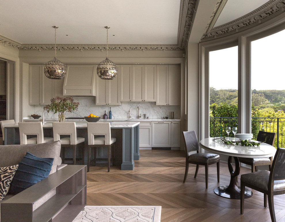 Example of a transitional galley medium tone wood floor open concept kitchen design in San Francisco with shaker cabinets, gray cabinets, white backsplash, stone slab backsplash and an island