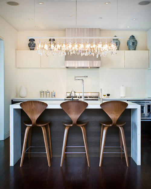 A long, horizonatal, chandelier pendant light over a 3 seating kitchen island in a white contemporary kitchen design.