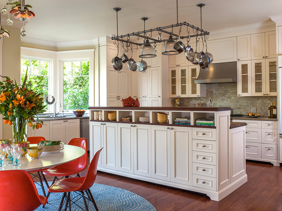 Eat-in kitchen - mid-sized transitional l-shaped medium tone wood floor eat-in kitchen idea in San Francisco with white cabinets, stainless steel countertops, green backsplash, stone tile backsplash and paneled appliances