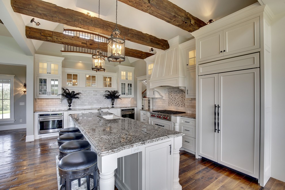 Example of a large classic l-shaped dark wood floor open concept kitchen design in Minneapolis with a farmhouse sink, white cabinets, an island, recessed-panel cabinets, white backsplash, paneled appliances and limestone backsplash