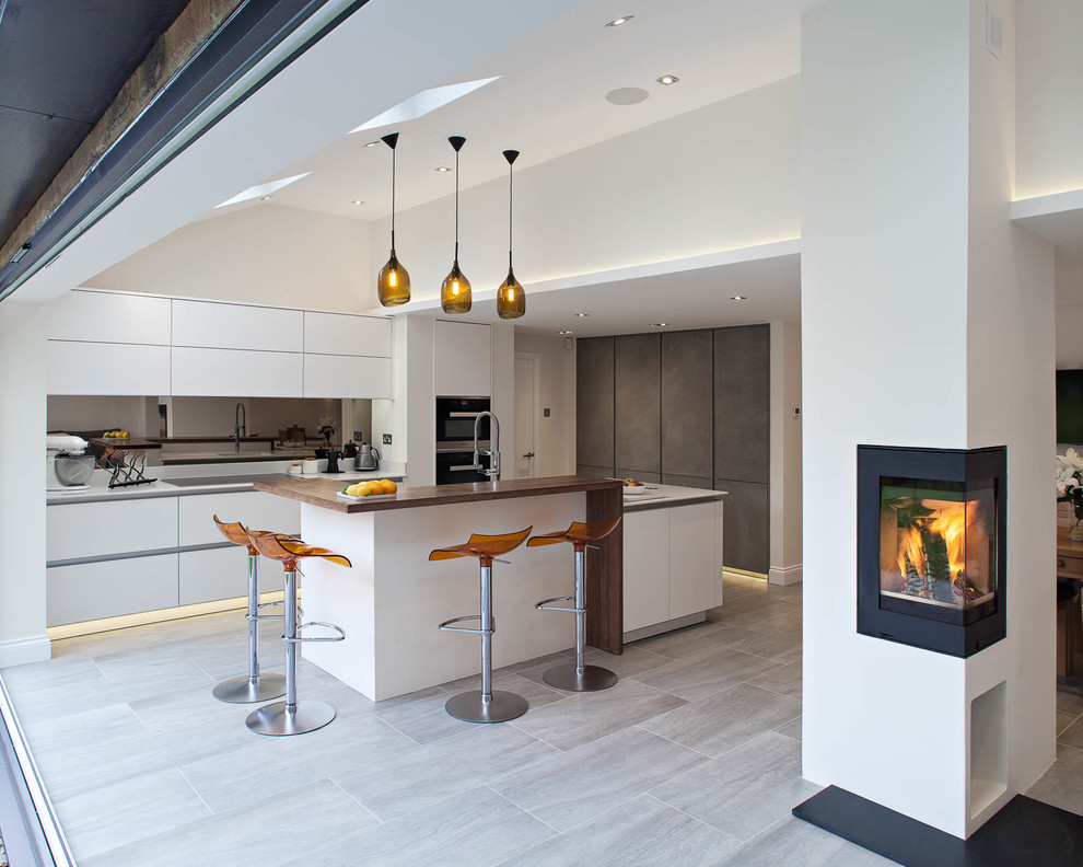 Mid-sized danish galley open concept kitchen photo in London with flat-panel cabinets, white cabinets and an island
