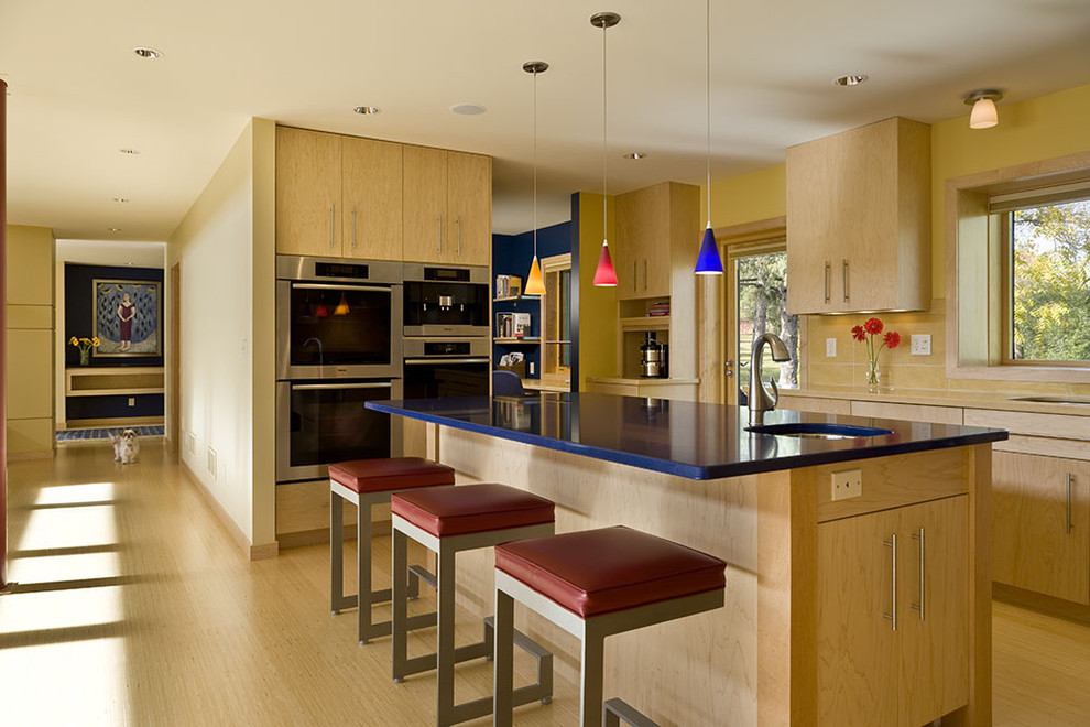Trendy kitchen photo in Minneapolis with stainless steel appliances, flat-panel cabinets, light wood cabinets and blue countertops