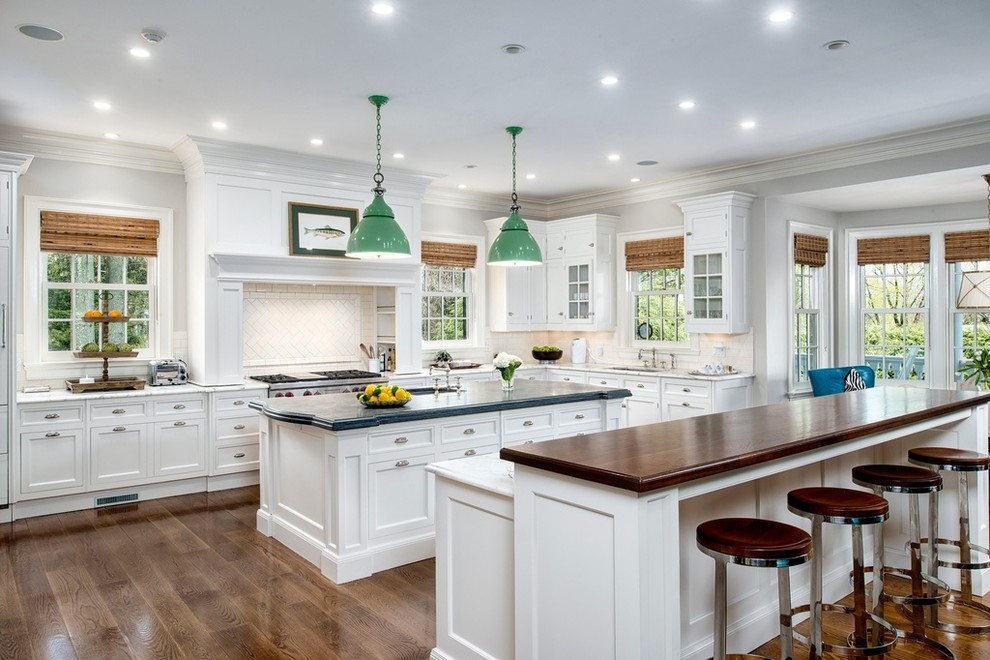 Elegant l-shaped medium tone wood floor kitchen photo in New York with an undermount sink, shaker cabinets, white cabinets, white backsplash, ceramic backsplash, stainless steel appliances, two islands and wood countertops