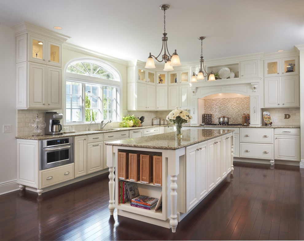 Example of a classic medium tone wood floor kitchen design in Providence with mosaic tile backsplash, granite countertops, beige backsplash, white cabinets and raised-panel cabinets