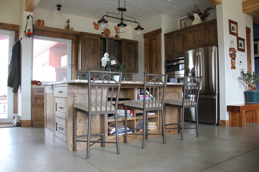 Mid-sized country l-shaped concrete floor open concept kitchen photo in Salt Lake City with a farmhouse sink, distressed cabinets, granite countertops, multicolored backsplash, stone tile backsplash, stainless steel appliances and an island