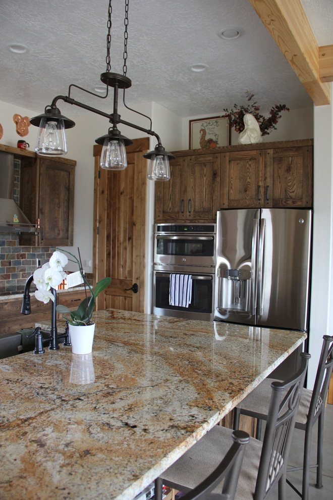 Inspiration for a mid-sized cottage l-shaped concrete floor open concept kitchen remodel in Salt Lake City with a farmhouse sink, distressed cabinets, granite countertops, multicolored backsplash, stone tile backsplash, stainless steel appliances and an island