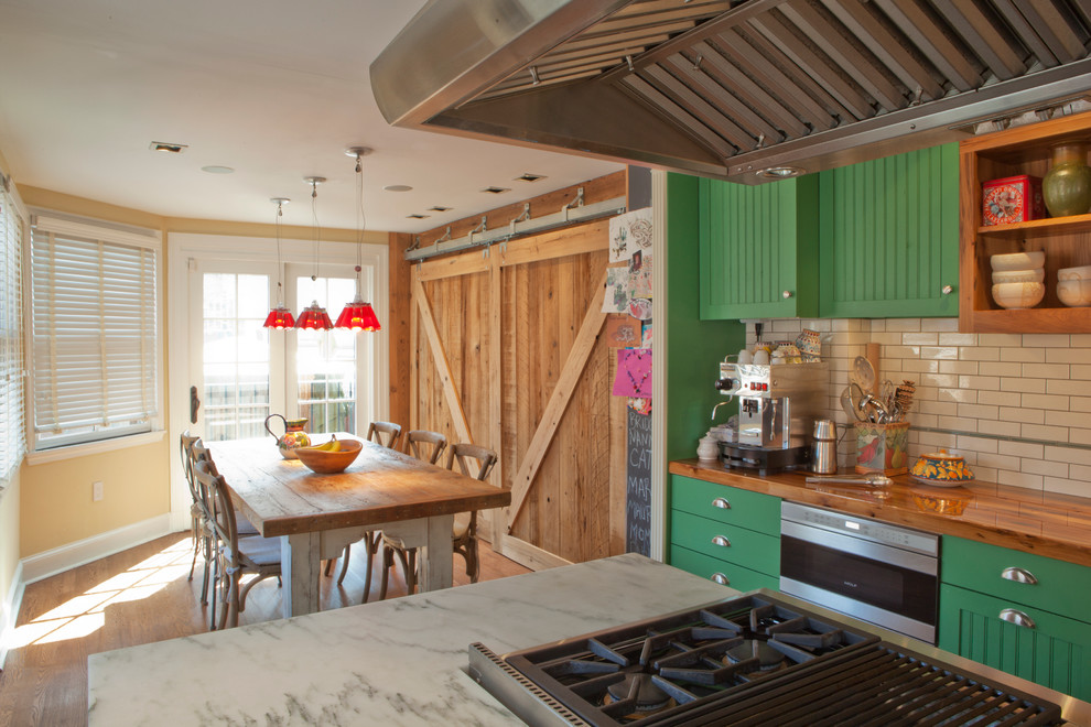 Inspiration for a timeless eat-in kitchen remodel in Philadelphia with subway tile backsplash, wood countertops, green cabinets and stainless steel appliances