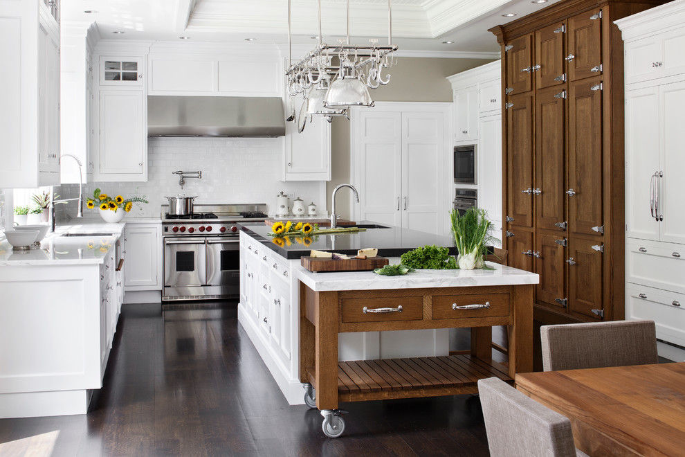 Inspiration for a large timeless u-shaped dark wood floor eat-in kitchen remodel in Boston with a farmhouse sink, shaker cabinets, white cabinets, marble countertops, white backsplash, subway tile backsplash and stainless steel appliances