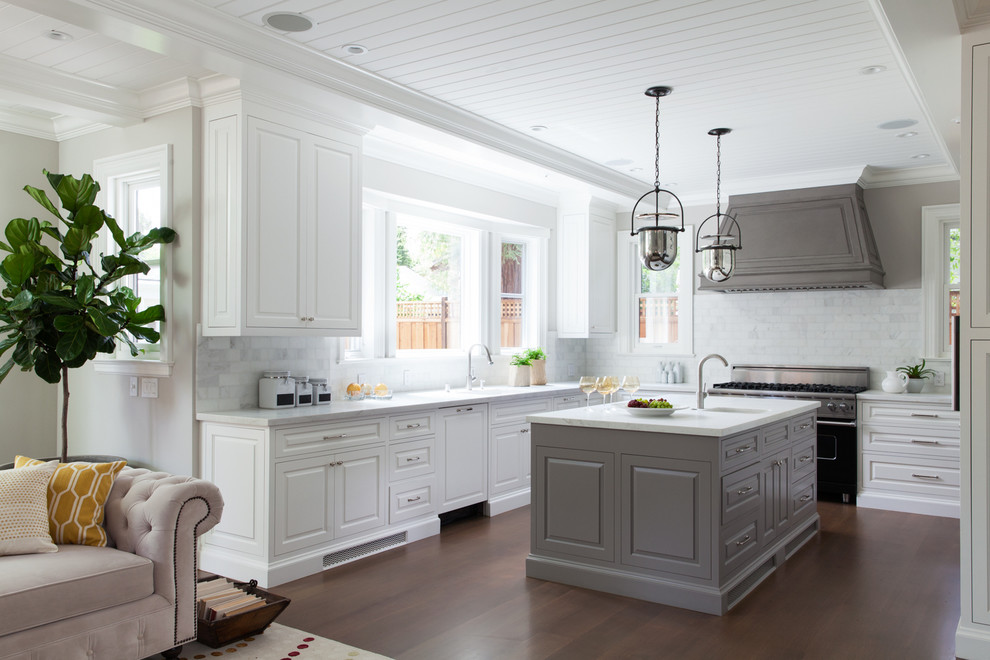 Inspiration for a timeless u-shaped dark wood floor open concept kitchen remodel in San Francisco with white cabinets, marble countertops, white backsplash, black appliances, an island and raised-panel cabinets