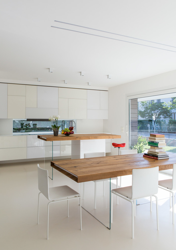 Inspiration for a mid-sized modern white floor eat-in kitchen remodel in Other with flat-panel cabinets, white cabinets, wood countertops, mirror backsplash, an undermount sink and an island