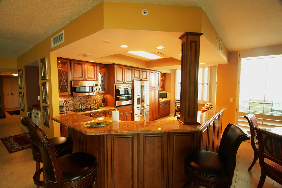 Example of a classic u-shaped ceramic tile kitchen design in Miami with raised-panel cabinets, medium tone wood cabinets, stone tile backsplash, stainless steel appliances and an island