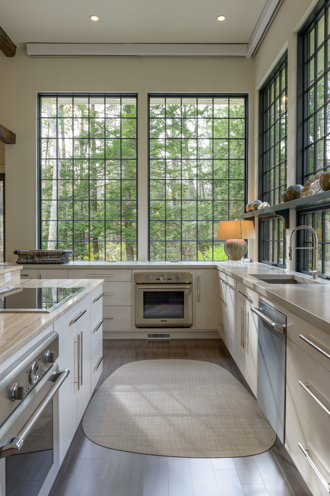 Transitional l-shaped kitchen photo in Manchester with flat-panel cabinets, beige cabinets and an island