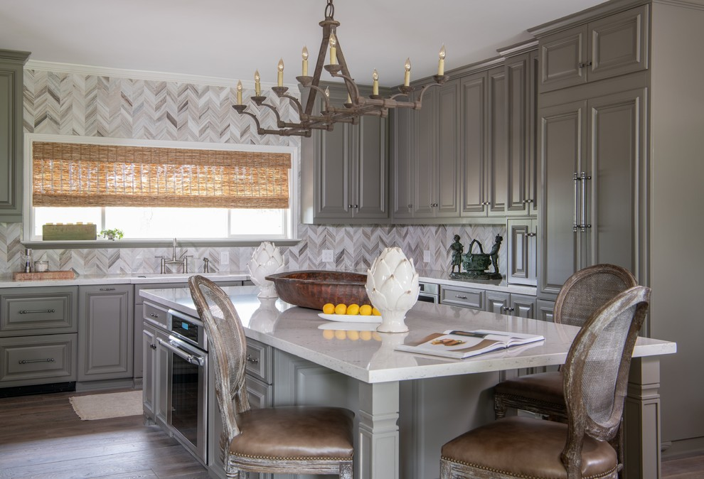 Elegant l-shaped medium tone wood floor and brown floor eat-in kitchen photo in Austin with an undermount sink, raised-panel cabinets, gray cabinets, beige backsplash, mosaic tile backsplash, paneled appliances, an island and white countertops