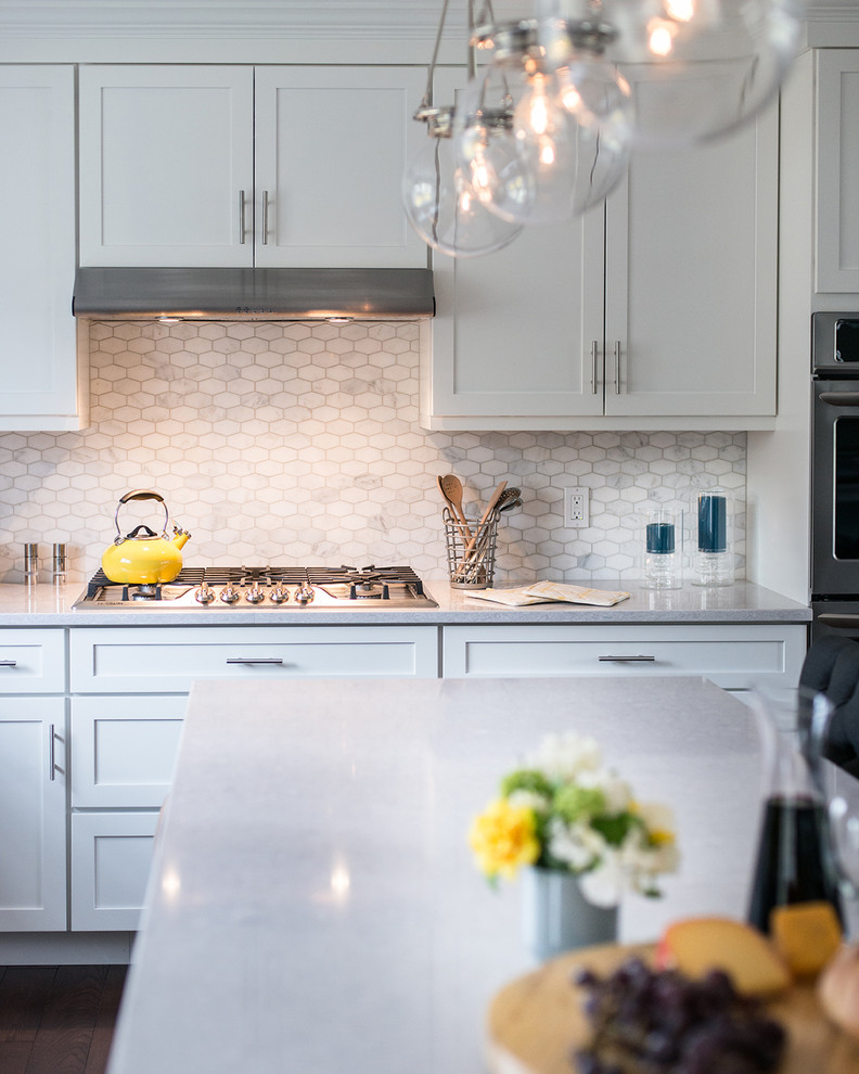 Large transitional l-shaped dark wood floor open concept kitchen photo in New York with a drop-in sink, shaker cabinets, white cabinets, quartzite countertops, white backsplash, mosaic tile backsplash, stainless steel appliances and an island