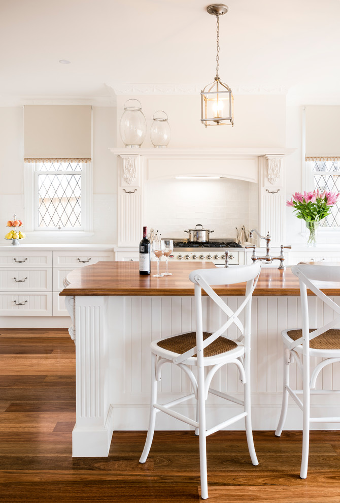 Eat-in kitchen - large farmhouse l-shaped medium tone wood floor and brown floor eat-in kitchen idea in Melbourne with a farmhouse sink, recessed-panel cabinets, white cabinets, wood countertops, white backsplash, ceramic backsplash, white appliances and an island