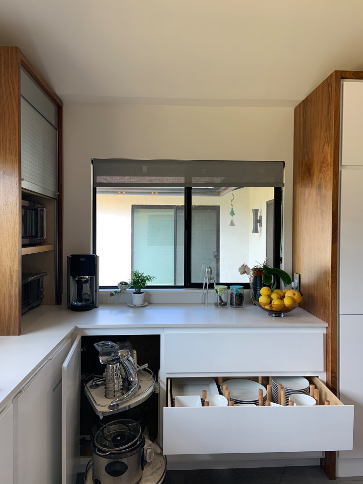 Mid-sized 1950s l-shaped porcelain tile, gray floor and vaulted ceiling open concept kitchen photo in San Diego with an undermount sink, flat-panel cabinets, white cabinets, quartz countertops, white backsplash, quartz backsplash, stainless steel appliances, an island and white countertops