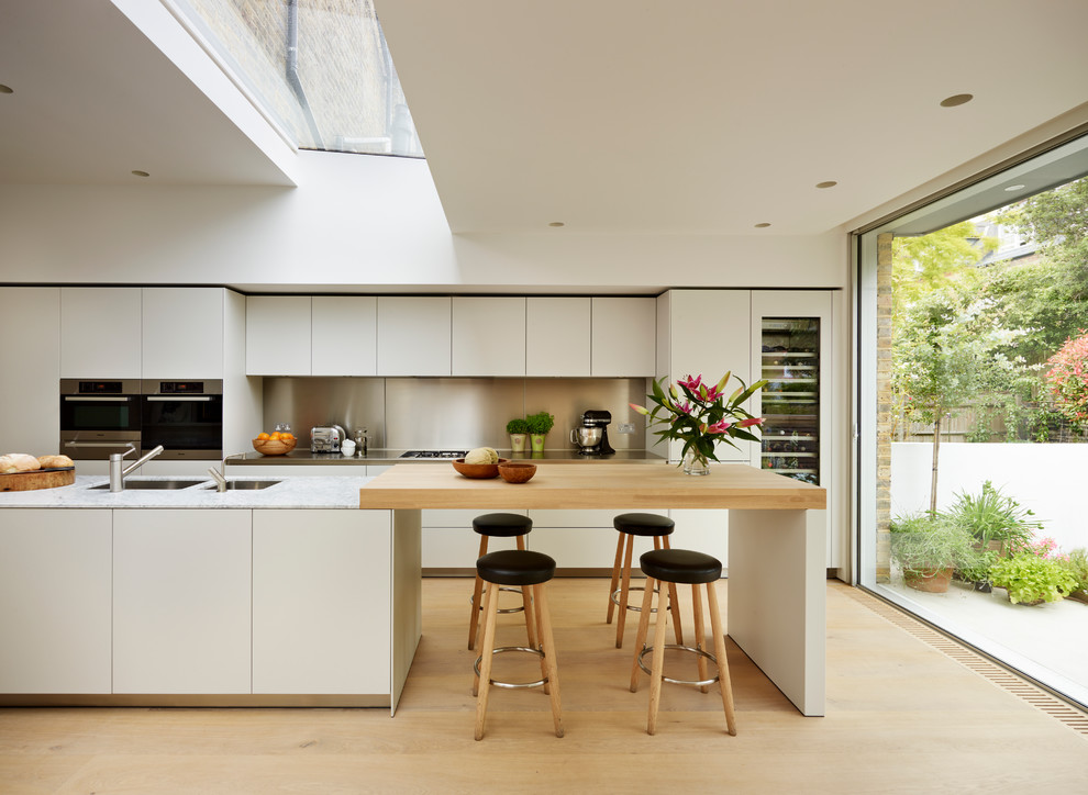 Example of a danish light wood floor kitchen design in London with flat-panel cabinets, white cabinets, an island and paneled appliances