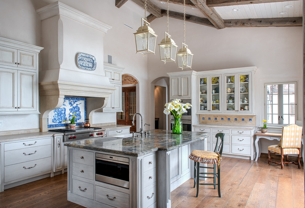 Example of a large farmhouse l-shaped light wood floor and brown floor enclosed kitchen design in San Francisco with glass-front cabinets, beige cabinets, multicolored backsplash, stainless steel appliances, an island, a farmhouse sink, quartzite countertops, ceramic backsplash and beige countertops