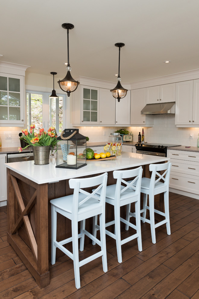 Example of a beach style dark wood floor kitchen design in Ottawa with shaker cabinets, white cabinets, white backsplash, subway tile backsplash and an island