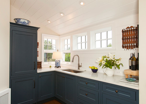 Transitional styled blue and white kitchen remodel by Savvy Cabinetry by Design featuring deep blue cabinets from Dura Supreme with white countertops, and wood floors.