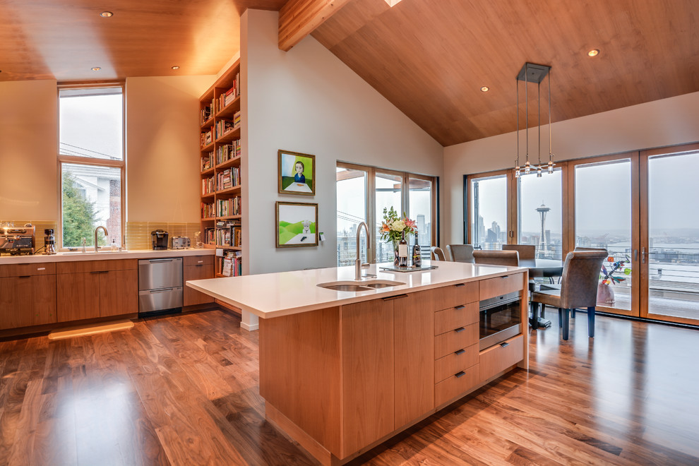 Example of a mid-sized minimalist medium tone wood floor eat-in kitchen design in Seattle with a double-bowl sink, flat-panel cabinets, medium tone wood cabinets, beige backsplash, ceramic backsplash, stainless steel appliances and an island
