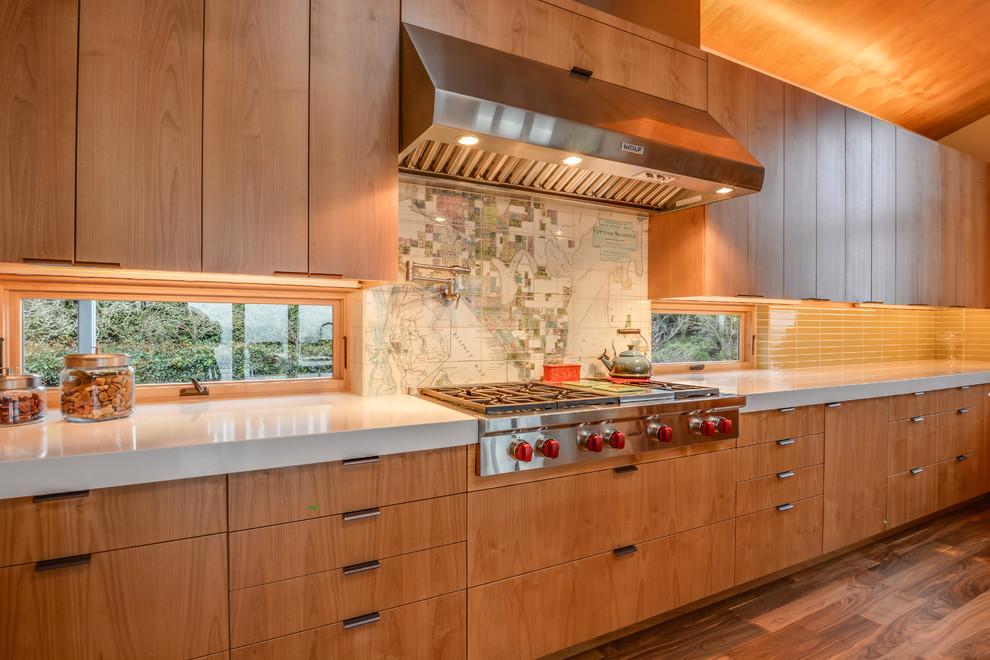Mid-sized minimalist medium tone wood floor eat-in kitchen photo in Seattle with a double-bowl sink, flat-panel cabinets, medium tone wood cabinets, beige backsplash, ceramic backsplash, stainless steel appliances and an island