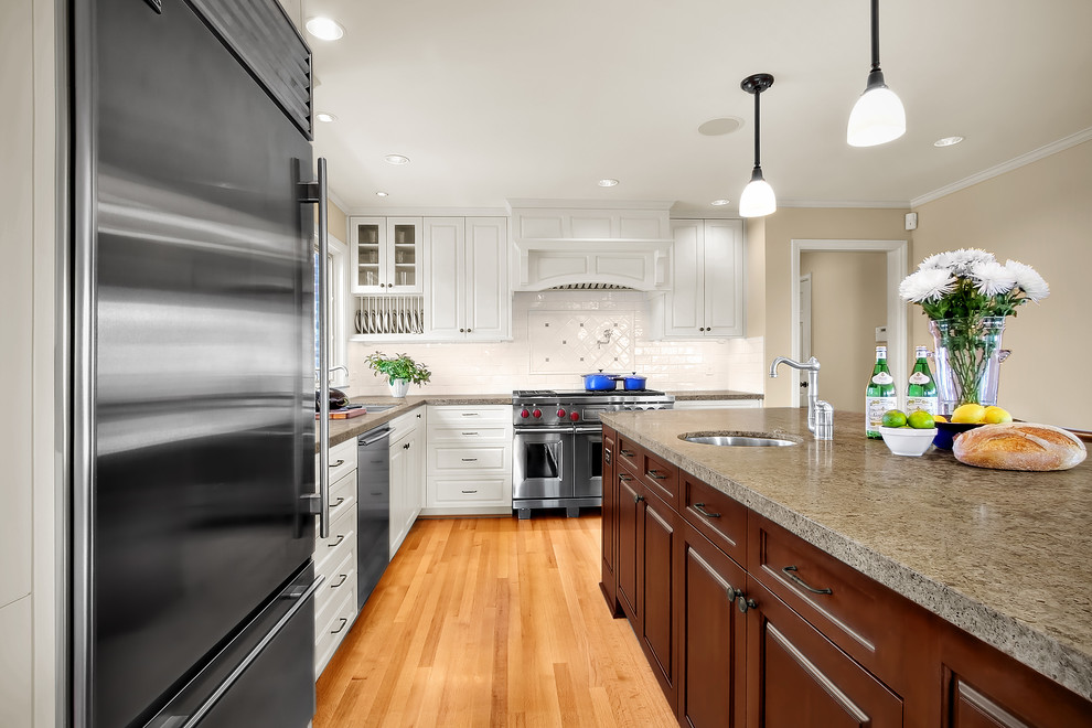 Inspiration for a timeless l-shaped kitchen remodel in Seattle with granite countertops, stainless steel appliances and white backsplash