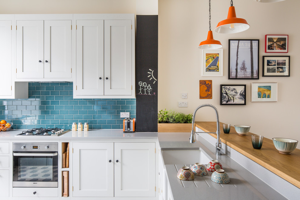 Small transitional l-shaped ceramic tile and multicolored floor kitchen photo in London with a farmhouse sink, shaker cabinets, white cabinets, quartz countertops, blue backsplash, subway tile backsplash and stainless steel appliances