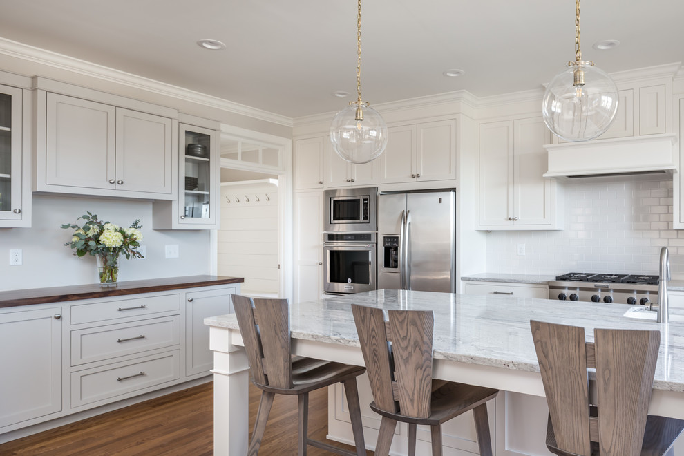 This is an example of a large transitional u-shaped eat-in kitchen in Raleigh with shaker cabinets, white cabinets, white splashback, stainless steel appliances, medium hardwood floors, an island, a farmhouse sink, brown floor, quartzite benchtops, subway tile splashback and white benchtop.