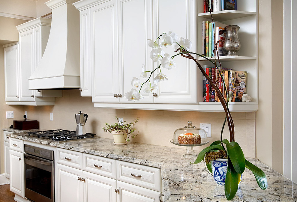 Elegant kitchen photo in Tampa with granite countertops, white cabinets and beige backsplash