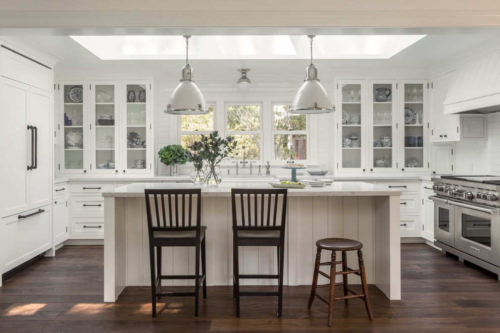 Example of a mid-sized country u-shaped dark wood floor kitchen design in San Francisco with glass-front cabinets, white cabinets, white backsplash, stainless steel appliances and an island