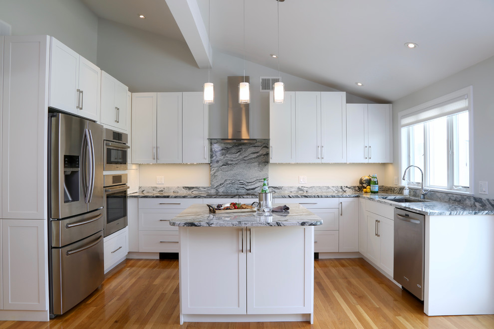 Inspiration for a mid-sized transitional u-shaped medium tone wood floor eat-in kitchen remodel in Providence with an undermount sink, shaker cabinets, white cabinets, granite countertops, white backsplash, stone slab backsplash, stainless steel appliances and an island