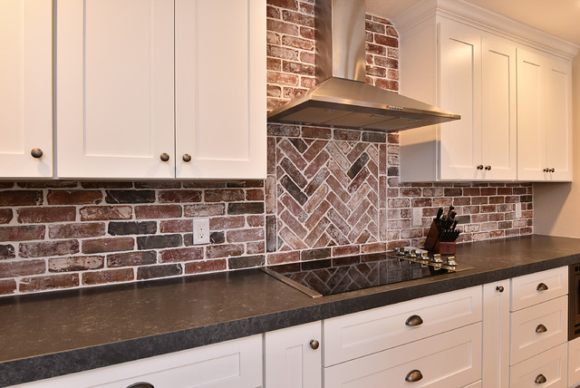 Example of a large cottage l-shaped light wood floor and brown floor open concept kitchen design in Phoenix with a farmhouse sink, shaker cabinets, white cabinets, quartz countertops, red backsplash, brick backsplash, stainless steel appliances and an island