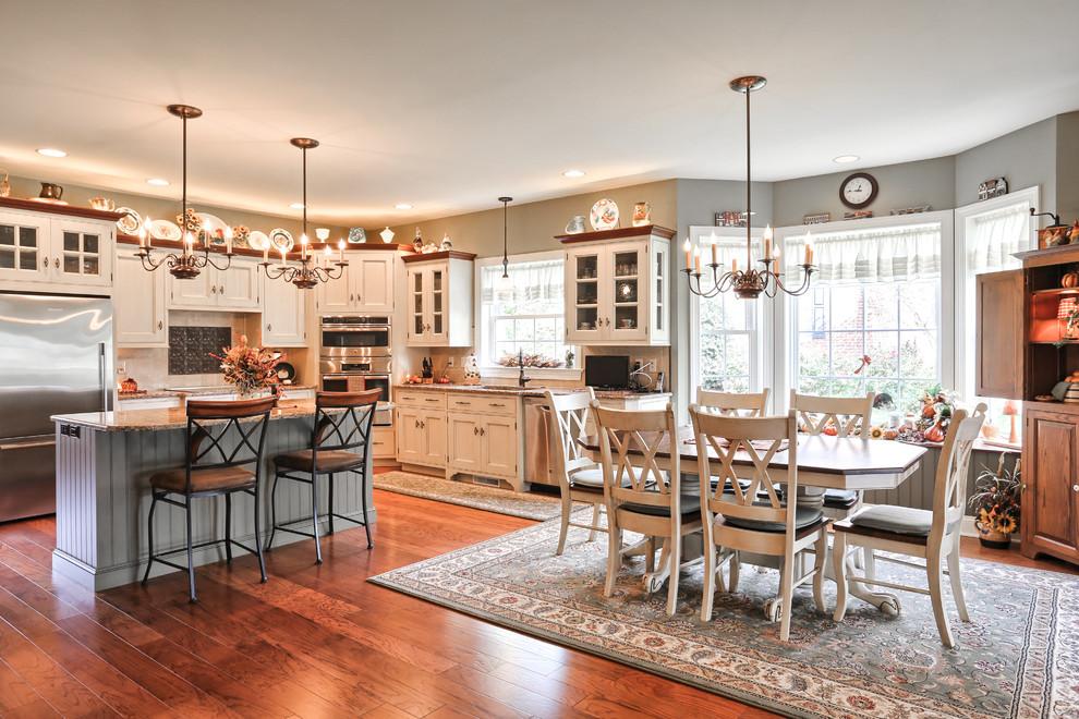 Diseño de cocina tradicional con encimera de granito, electrodomésticos de acero inoxidable, suelo de madera en tonos medios, armarios con paneles empotrados, puertas de armario blancas y una isla