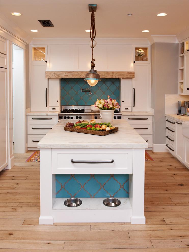 Kitchen - mediterranean u-shaped kitchen idea in San Diego with white cabinets, marble countertops, white backsplash and white countertops