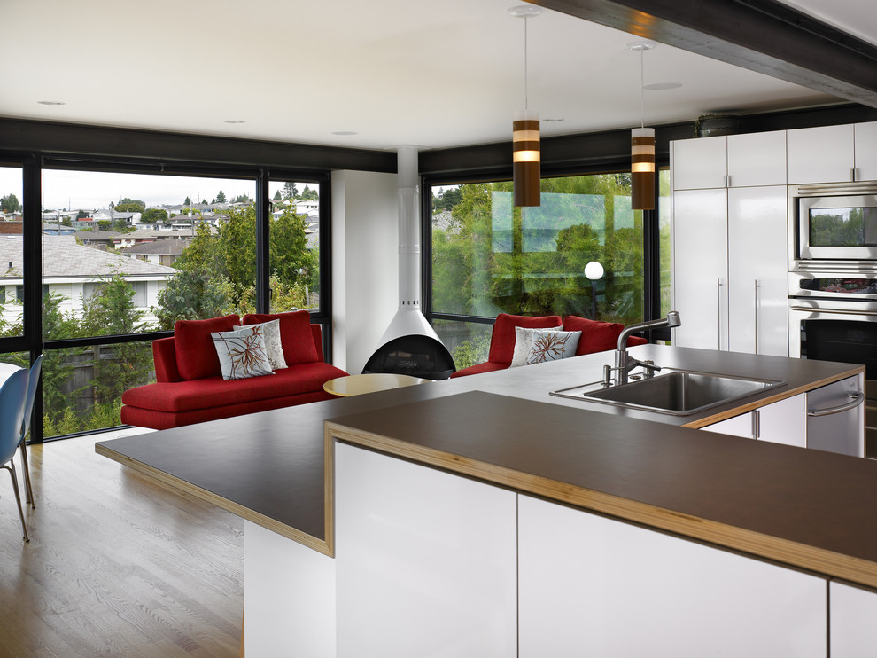 Example of a minimalist open concept kitchen design in Seattle with a drop-in sink, flat-panel cabinets, white cabinets, laminate countertops and stainless steel appliances