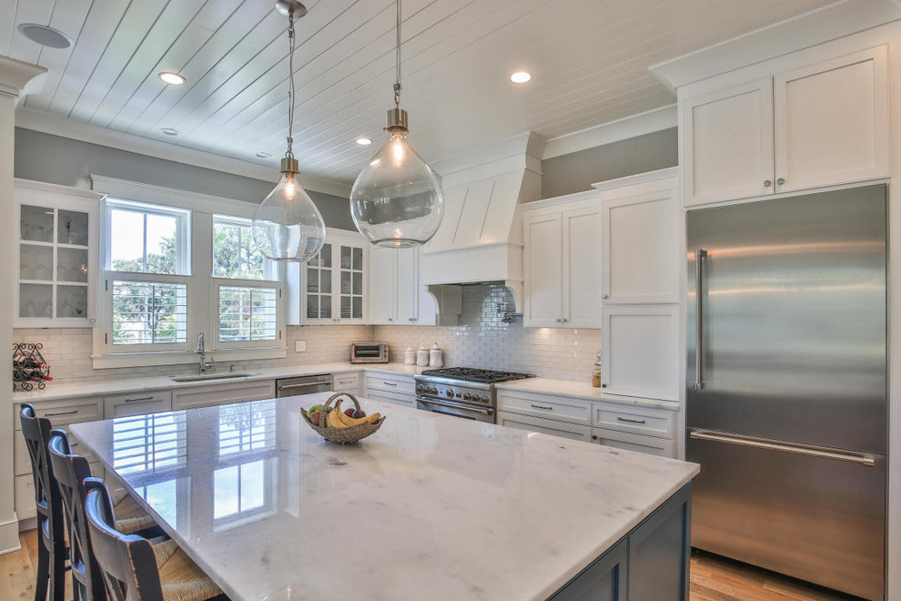 Example of a beach style l-shaped medium tone wood floor and brown floor kitchen design in Charleston with an undermount sink, shaker cabinets, white cabinets, white backsplash, subway tile backsplash, stainless steel appliances and an island