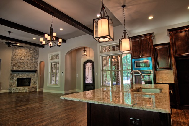 Large transitional l-shaped medium tone wood floor and brown floor open concept kitchen photo in Dallas with an undermount sink, raised-panel cabinets, dark wood cabinets, granite countertops, white backsplash, stone tile backsplash, stainless steel appliances and an island