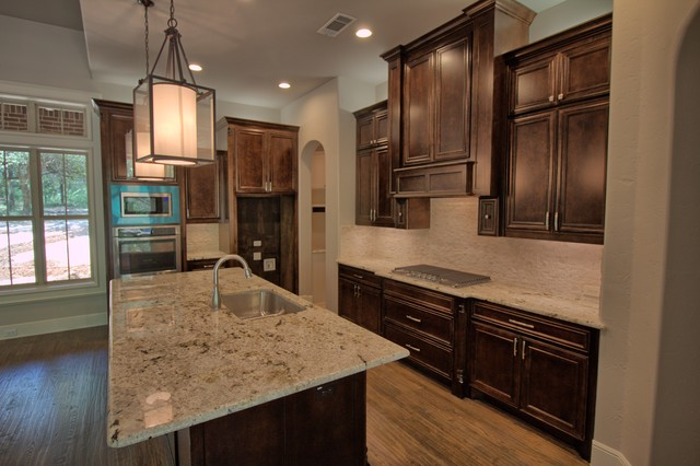 Example of a large transitional l-shaped medium tone wood floor open concept kitchen design in Dallas with an undermount sink, raised-panel cabinets, dark wood cabinets, granite countertops, white backsplash, stone tile backsplash, stainless steel appliances and an island