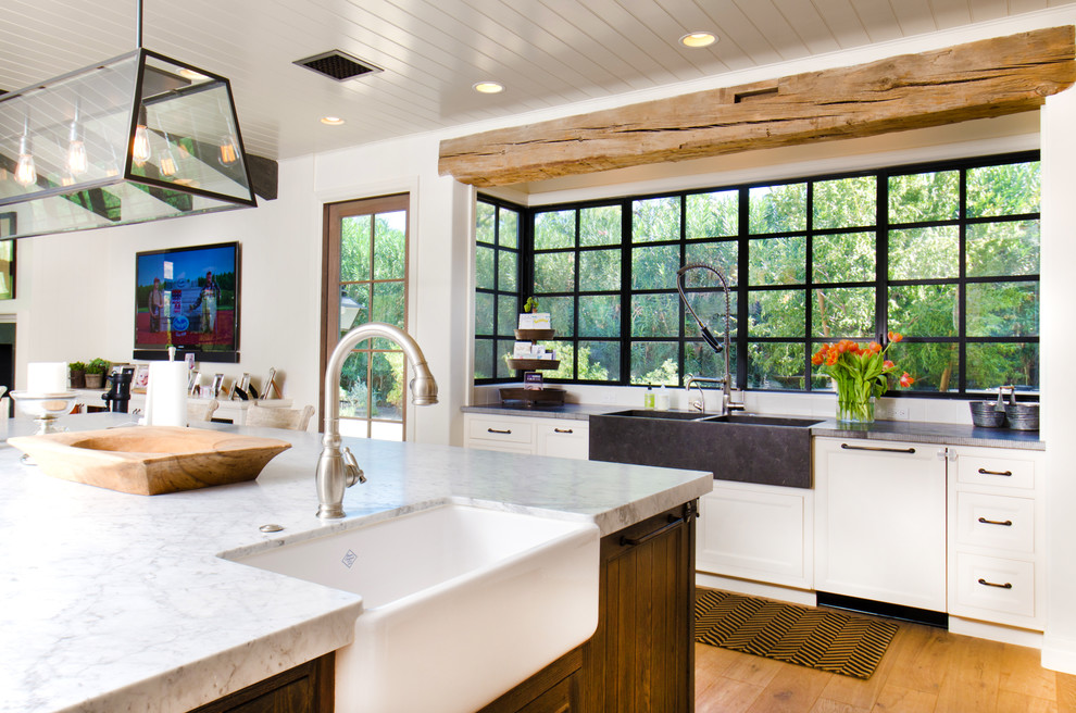 Example of a farmhouse l-shaped medium tone wood floor open concept kitchen design in Phoenix with a farmhouse sink, shaker cabinets, white cabinets and an island