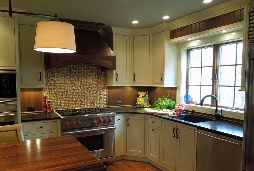 Open concept kitchen - mid-sized traditional l-shaped medium tone wood floor open concept kitchen idea in Charleston with a single-bowl sink, beaded inset cabinets, white cabinets, granite countertops, brown backsplash, stainless steel appliances and an island