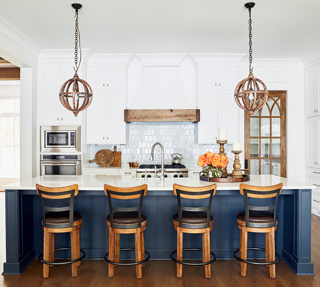 Inspiration for a beach style kitchen in Raleigh with shaker cabinets, white cabinets, white splashback, stainless steel appliances, medium hardwood flooring, an island and white worktops.