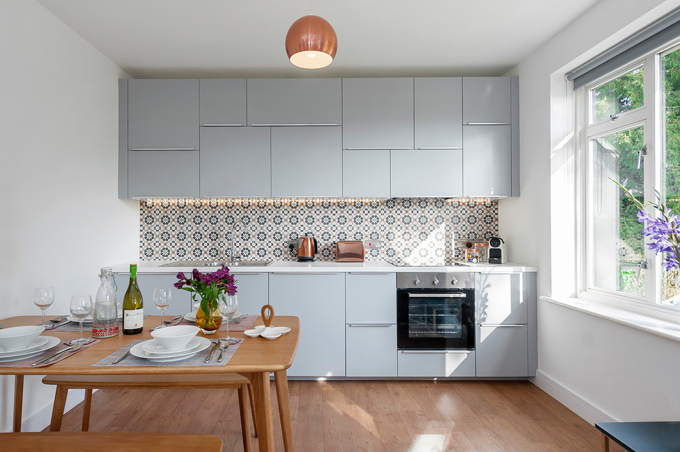 Small trendy single-wall light wood floor and brown floor eat-in kitchen photo in Wiltshire with flat-panel cabinets, blue cabinets, stainless steel appliances, a drop-in sink and multicolored backsplash