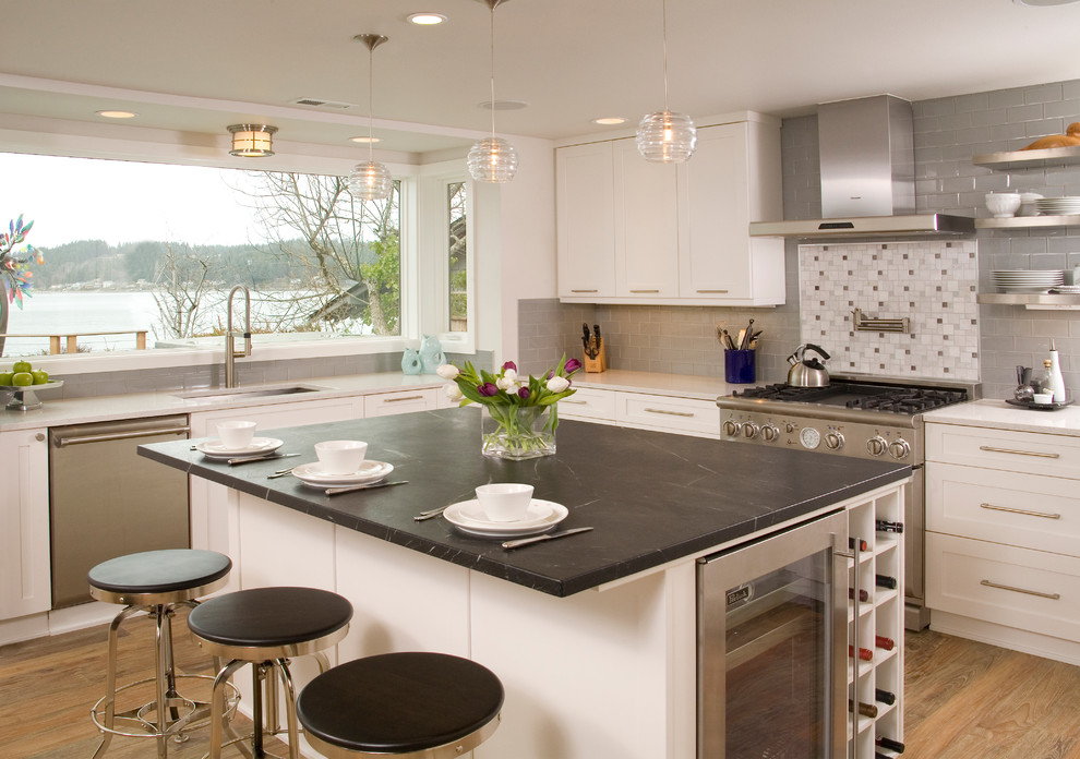 Eat-in kitchen - mid-sized transitional l-shaped medium tone wood floor and brown floor eat-in kitchen idea in Seattle with an undermount sink, white cabinets, soapstone countertops, shaker cabinets, an island, multicolored backsplash, mosaic tile backsplash and paneled appliances
