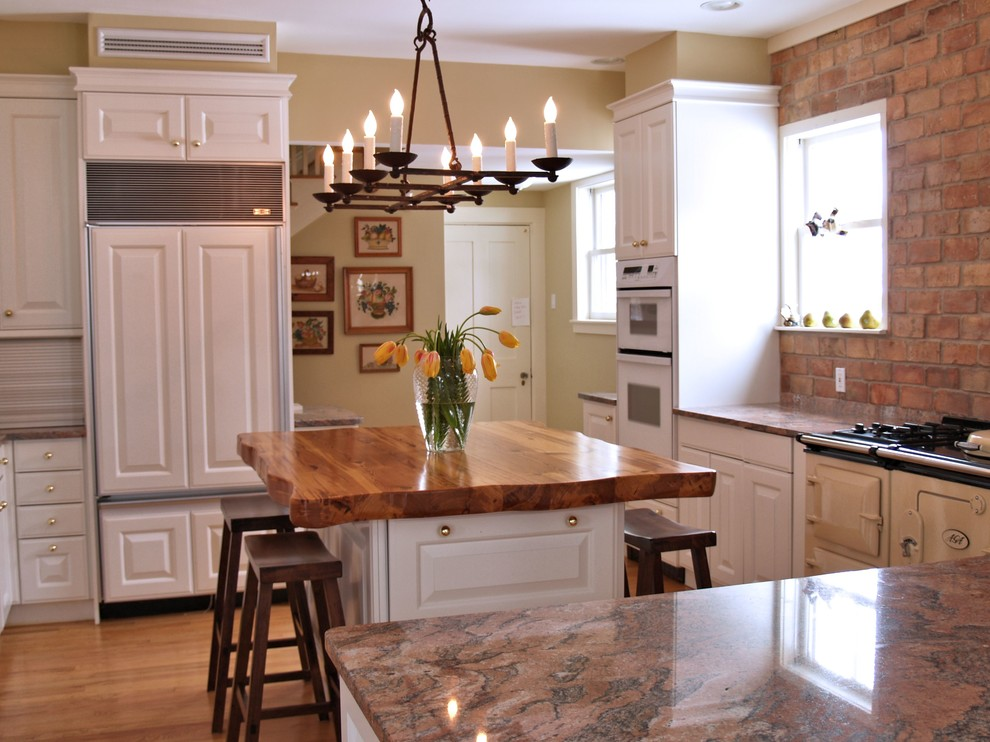 Inspiration for a large country l-shaped light wood floor eat-in kitchen remodel in Austin with raised-panel cabinets, white cabinets, wood countertops, beige backsplash, colored appliances and an island