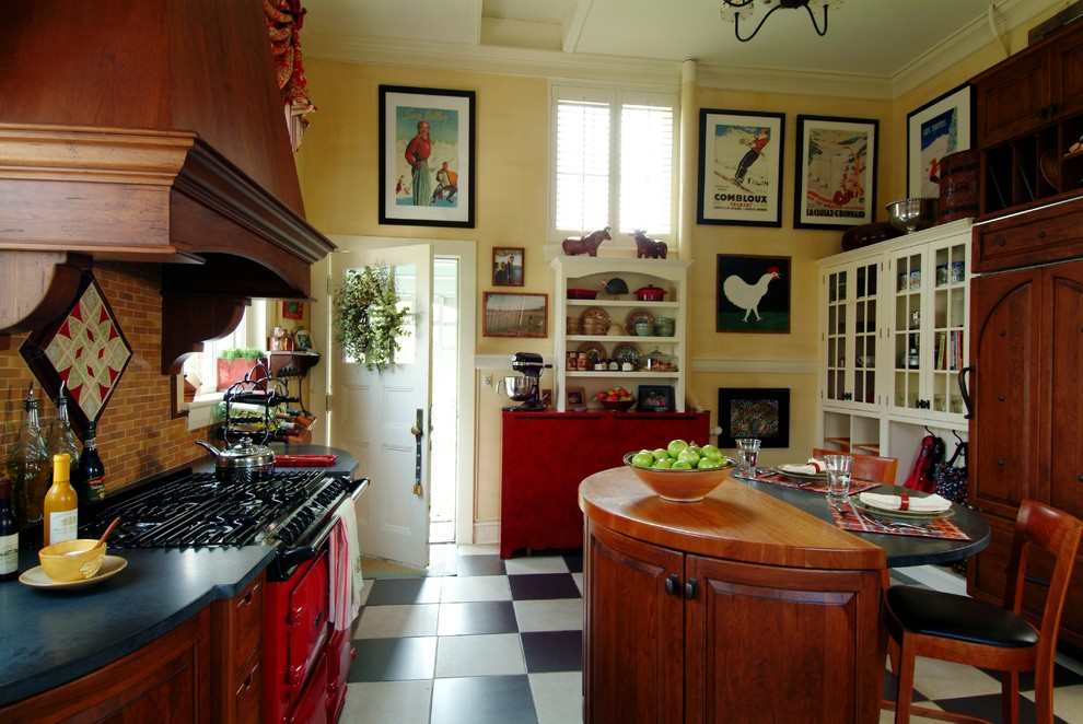 Example of a mid-sized classic l-shaped ceramic tile and multicolored floor eat-in kitchen design in Boston with beaded inset cabinets, colored appliances, a farmhouse sink, medium tone wood cabinets, granite countertops, brown backsplash, ceramic backsplash and an island