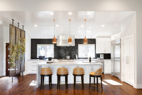 Big and open modern kitchen with white, black and copper colors featuring four stools with dot patterns on the stools