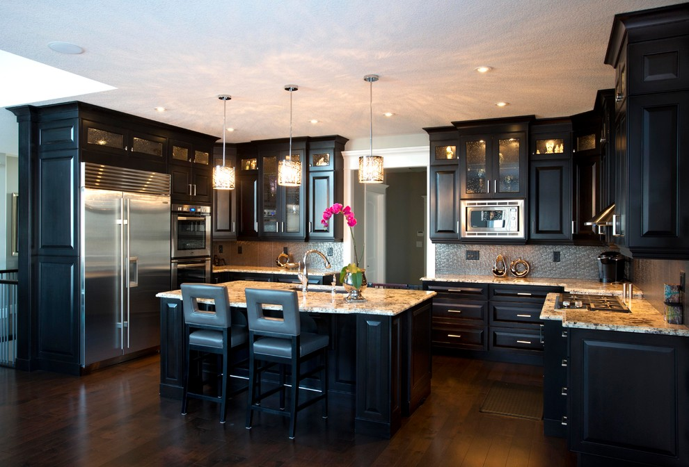 Transitional u-shaped enclosed kitchen photo in Calgary with an undermount sink, raised-panel cabinets, dark wood cabinets, granite countertops, metallic backsplash, porcelain backsplash and stainless steel appliances