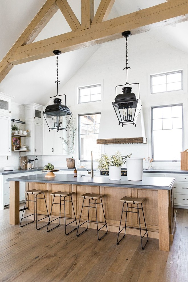 Large cottage u-shaped dark wood floor and brown floor kitchen photo in Salt Lake City with white cabinets, white backsplash, black appliances, an island, gray countertops and shaker cabinets