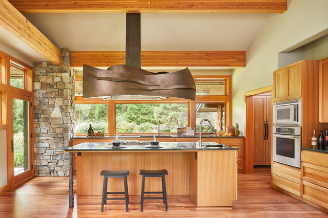 Example of a mountain style medium tone wood floor kitchen design in Seattle with medium tone wood cabinets, stainless steel appliances, an island, shaker cabinets and window backsplash